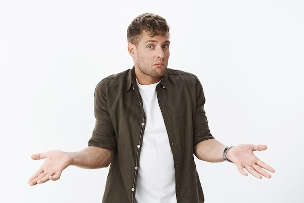 Clueless guy shrugging shoulders as being unaware. portrait of confused cute blond man holding hands sideways dazed, pursing lips and lifting eyebrows questioned against gray wall
