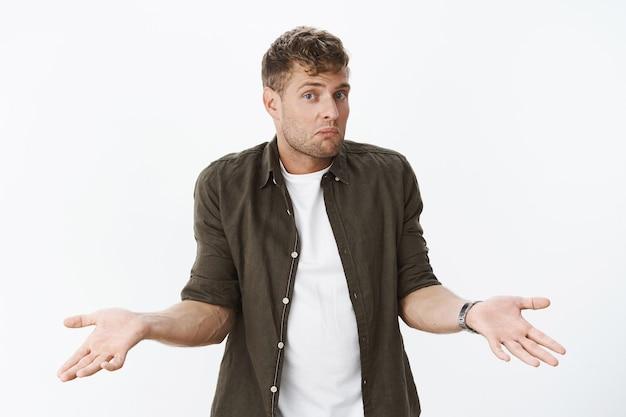 눈치 채지 못한 채 어깨를 으쓱하는 멍청한 남자. 회색 벽에 대해 질문을 받고 입술을 오므리고 눈썹을 들어올리는 혼란스러운 귀여운 금발 남자의 초상화