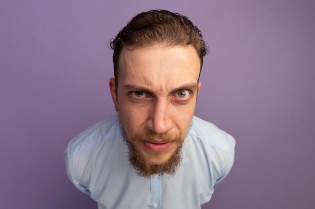 Uomo biondo bello all'oscuro che esamina fronte isolato sulla parete viola