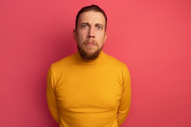 L'uomo biondo bello senza tracce esamina la macchina fotografica sul colore rosa