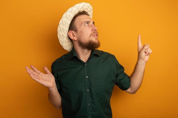 ビーチ帽子をかぶった無知なハンサムなブロンドの男は、オレンジ色の壁に隔離された手を開いて見ていると上向きを保持します。