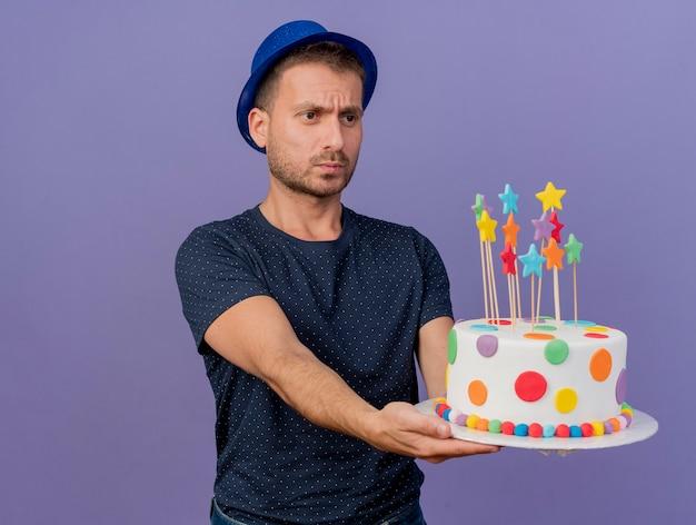 파란색 모자를 쓰고 우 둔 잘 생긴 백인 남자가 보유하고 복사 공간이 보라색 배경에 고립 된 생일 케이크를 본다