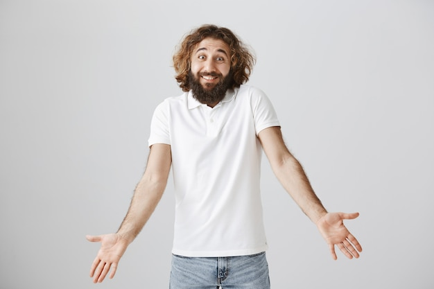 Clueless handsome middle-eastern man with long beard, shrugging puzzled