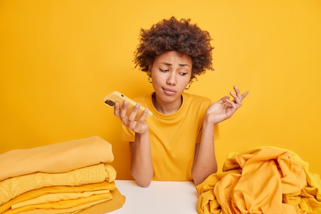 Clueless hesitant afro american woman shrugs shoulders doesnt know what to do with unused clothes looks at pile of unfolded laundry sits at table holds smartphone isolated on yellow