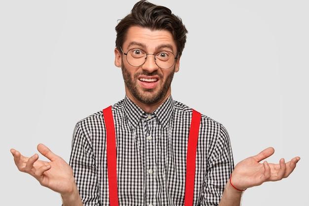 Un maschio esitante e incapace con un taglio di capelli alla moda, indossa abiti e occhiali alla moda, alza le spalle con incertezza, fa la scelta, isolato su un muro bianco. persone e concetto di linguaggio del corpo