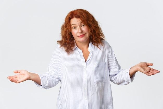 Clueless, indecisive cute middle-aged lady with red hair dont know, being unaware, shrugging and spread hands sideways confused, smiling as telling sorry have no idea, white wall