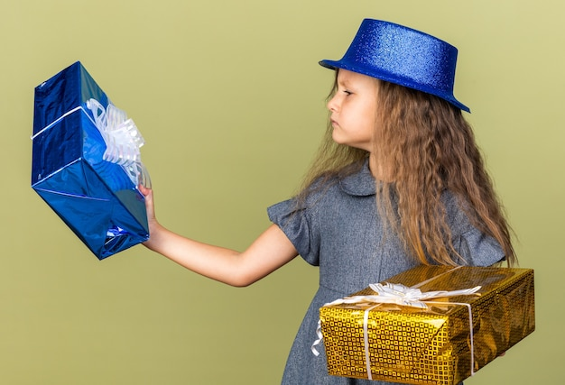 Clueless little blonde girl with blue party hat holding and looking at gift boxes isolated on olive green wall with copy space