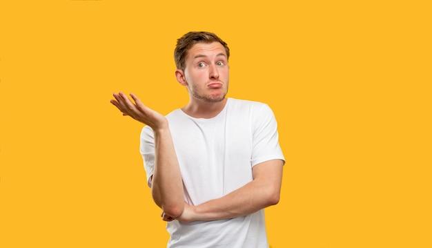 Бестолковый мужской портрет. без понятия. сомнительный парень пожимает плечами жест, изолированные на оранжевом фоне.