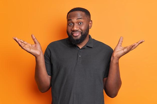 Бестолковый мужчина с бородой раздвигает ладони, пожимает плечами, смотрит в неведении, сталкивается с трудным выбором, одетый в повседневную черную футболку, изолированную над ярко-оранжевой стеной