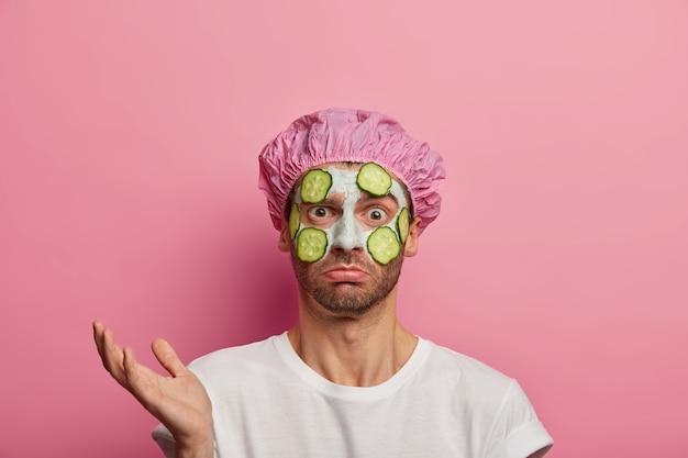 어리둥절한 얼굴 표정의 우둔한 남자, 손바닥을 들어, 카메라를 헷갈 리게 보며, 피부 상태를 개선하는 방법을 모르고, 목욕 모자를 쓰고