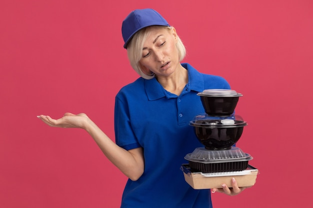 Clueless middle-aged blonde delivery woman in blue uniform and cap holding paper food package and food containers looking at them showing empty hand