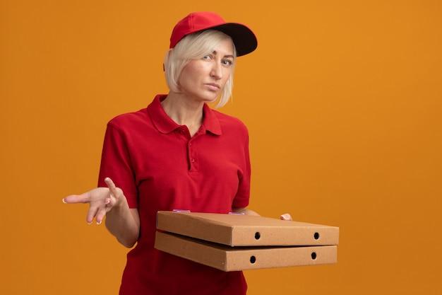 빨간 제복을 입은 단서가 없는 중년 금발 배달부와 피자 패키지를 들고 있는 모자를 쓴 모자는 복사 공간이 있는 주황색 벽에 고립된 빈 손을 보여주는 정면을 바라보고 있습니다.