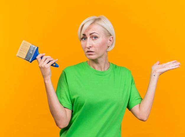 黄色の背景で隔離の空の手を示すペイントブラシを保持しているカメラを見て無知な中年金髪スラブ女性