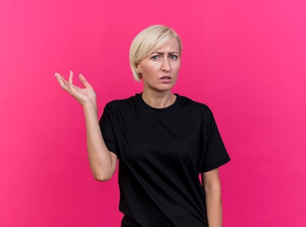 Clueless donna slava bionda di mezza età che mostra la mano vuota guardando la parte anteriore isolata sulla parete rosa con lo spazio della copia