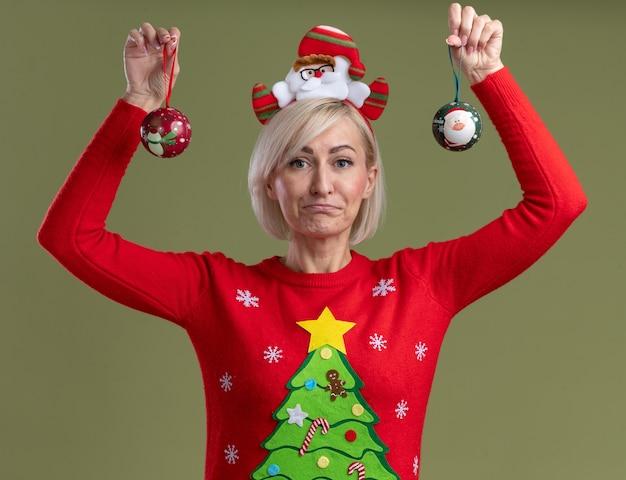 Clueless donna bionda di mezza età che indossa la fascia di babbo natale e maglione di natale sollevando palline di natale guardando la telecamera isolata su sfondo verde oliva