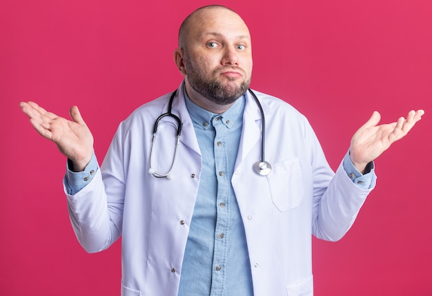 Clueless middle-aged male doctor wearing medical robe and stethoscope  doing i don't know gesture isolated on pink wall
