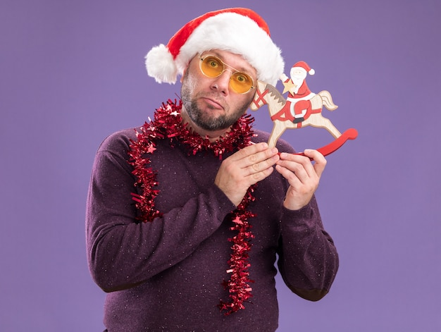 Clueless middle-aged man wearing santa hat and tinsel garland around neck with glasses holding santa on rocking horse figurine touching head with it  isolated on purple wall