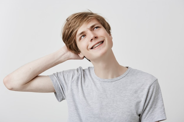 Clueless perplexed young caucasian man in grey t-shirt with fair hair and blue eyes looking upwards with confused and puzzled expression, scratching head, having forgot about girlfriend's birthday