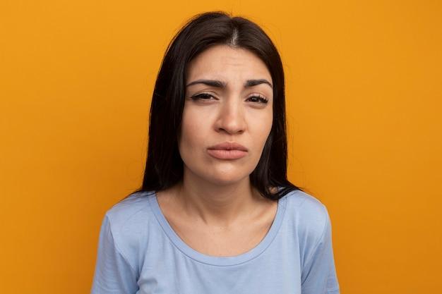 Невежественная симпатичная брюнетка женщина смотрит на фронт, изолированный на оранжевой стене