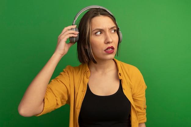 헤드폰에 우 둔 예쁜 백인 여자는 녹색 측면에서 보이는