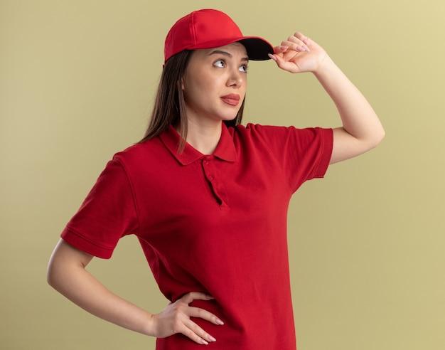 La bella donna delle consegne indifesa in uniforme mette la mano sul berretto e guarda di lato