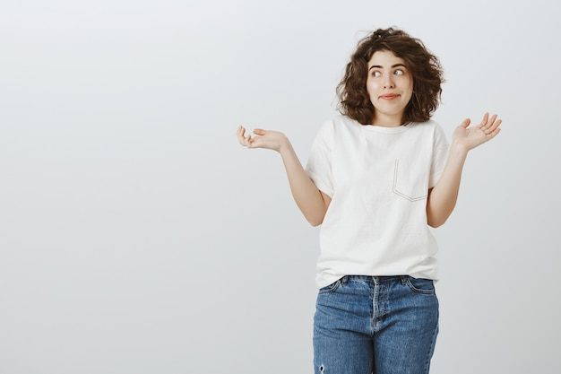 Clueless pretty girl shrugging with hands spread sideways, don't know anything, have no idea