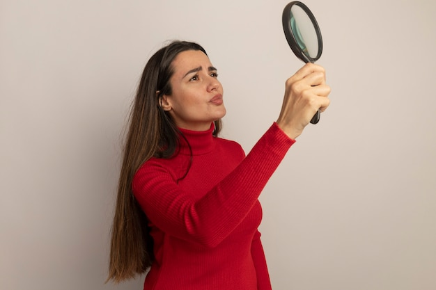 Clueless pretty woman holds and looks at magnifying glass isolated on white wall
