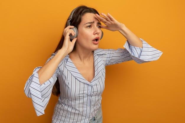헤드폰에 우 둔 예쁜 여자가 오렌지 벽에 고립 된 이마에 손바닥을 유지
