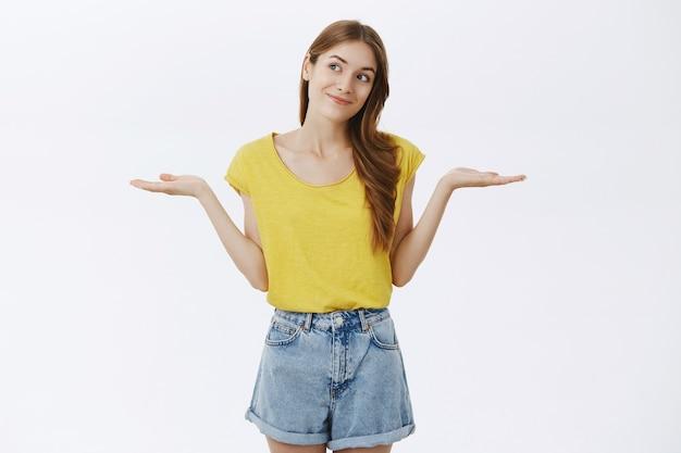 Бестолковая симпатичная молодая девушка в замешательстве пожимает плечами, все равно или не знает