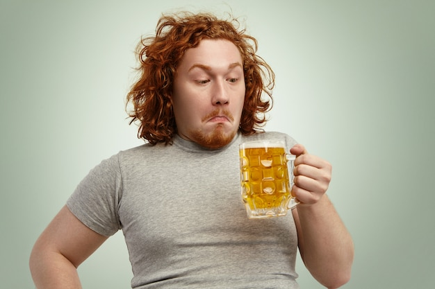 Clueless red haired young man with curly hair holding glass of light beer, looking at it, having confused indecisive expression, hesitating, thinking drink it or not, standing against blank wall