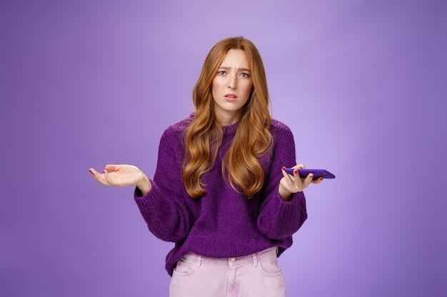 Incapace e triste donna rossa carina allargò le mani lateralmente accigliata disturbata e sconvolta tenendo lo smartphone interrogato e all'oscuro del motivo per cui il telefono cellulare non funziona, in posa sul muro viola.