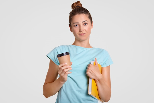 Clueless schoolgirl has puzzled uncertain expresion, holds takeaway coffee and book