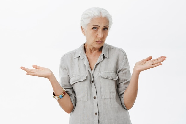Clueless senior woman shrugging unaware, spread hands sideways confused