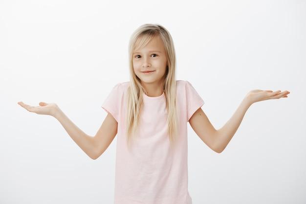 無知な肩をすくめる小さな女性は何も知らず、笑顔