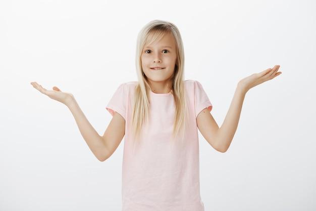 Бестолковый глупый ребенок пожимает плечами и смущенно улыбается