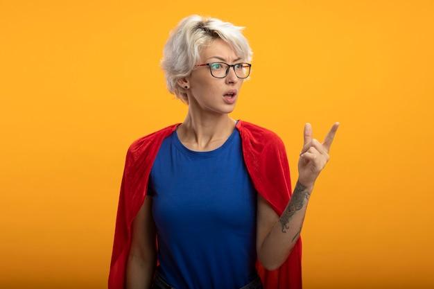 Бестолковая суперженщина в красной накидке в оптических очках смотрит и указывает в сторону, изолированную на оранжевой стене