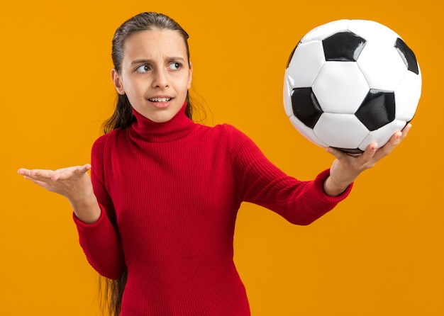 Clueless teenage girl stretching out soccer ball looking at it showing empty hand isolated on orange wall