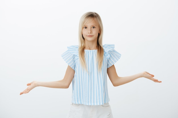 Clueless troubled little girl with blond hair in trendy blue blouse, spreading hands and shrugging with confused and unaware expression, being unable to answer over gray wall