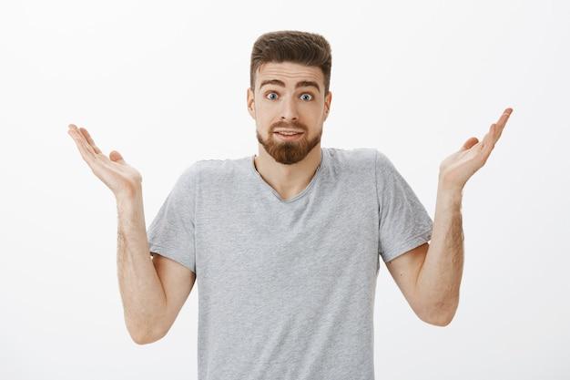 Невежественный невежественный красивый бородатый мужчина, пожимая плечами, подняв руки и брови с глупым невежественным выражением лица, не может ответить на вопрос, запутавшись над серой стеной