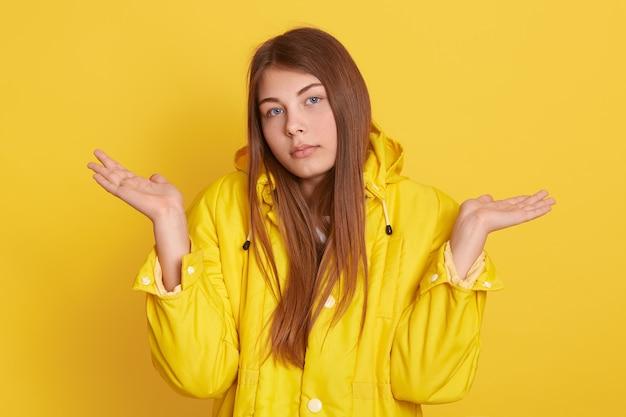 Бестолковая невежественная женщина с длинными волосами, в сомнении разводит ладони на желтом