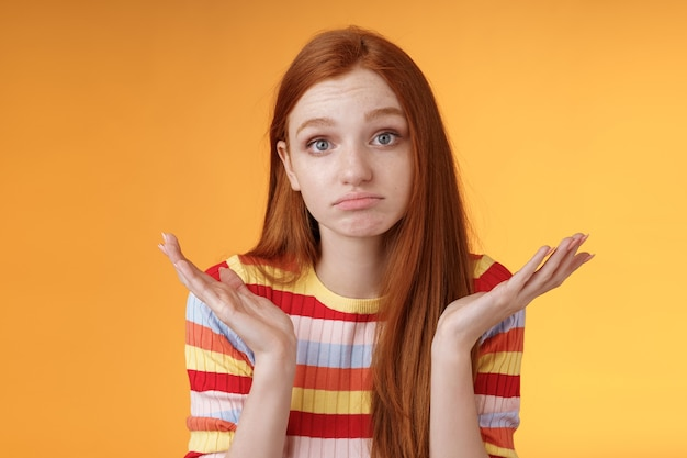 Clueless upset redhead young cute female coworker shrugging hands spread sideays unaware pouting confused cannot answer question apologizing not knowing, standing orange background