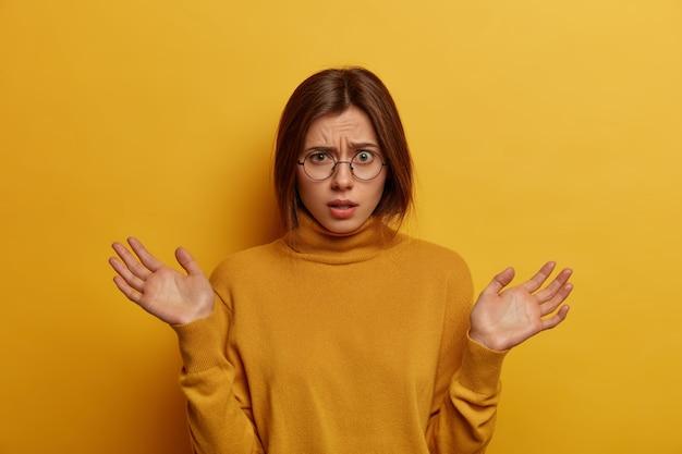 Невежественная женщина разводит ладони, вопросительное выражение лица, недоумевает трудная ситуация, носит повседневный полонек, изолированный на желтой стене. нерешительная европейская женщина выглядит нерешительно
