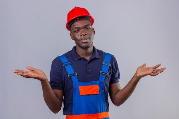 Бестолковый молодой афро-американский строитель в строительной форме и защитном шлеме пожимает плечами, выглядит неуверенно и смущенно, не имея ответа, разводя ладони стоя