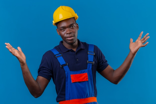 Clueless young african american builder man wearing construction uniform and safety helmet shrugging shoulders looking uncertain and confused having no answer spreading palms standing