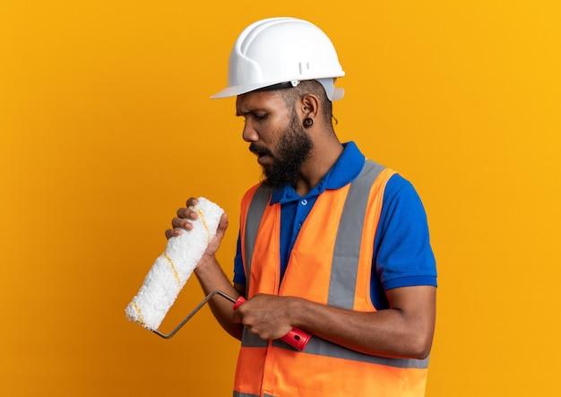 Clueless giovane afro-americano costruttore uomo in uniforme con casco di sicurezza che tiene e guardando il rullo di vernice isolato su sfondo arancione con spazio di copia