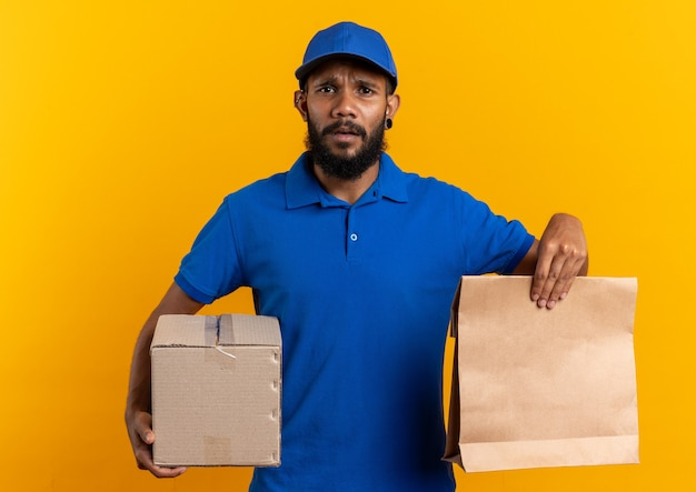 Clueless young afro-american delivery man holding cardboard box and food package isolated on orange background with copy space