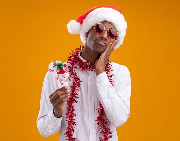 オレンジ色の背景で隔離のカメラを見て顔に手を保ちながらキャンディケインの飾りを保持している首の周りに見掛け倒しの花輪とサンタの帽子と眼鏡を身に着けている無知な若いアフリカ系アメリカ人の男