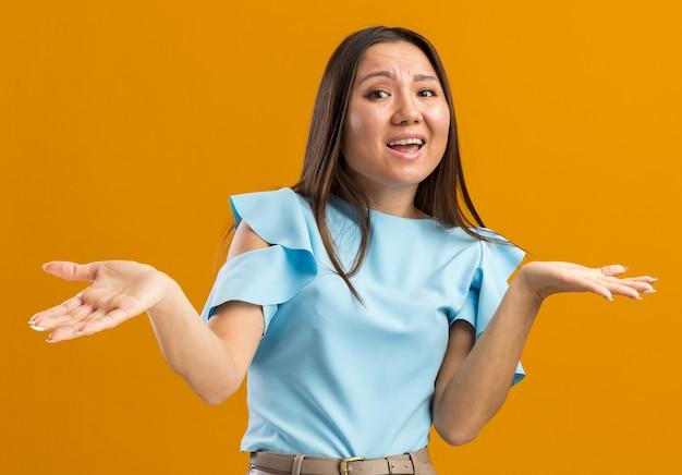 주황색 벽에 고립된 빈 손을 보여주는 앞을 바라보는 단서 없는 젊은 아시아 여성