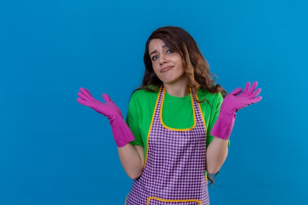 青の上に立って手のひらを広げて答えがわからないと混乱して混乱しているエプロンと手袋に肩をすくめて手袋で無知な若い美しい女性