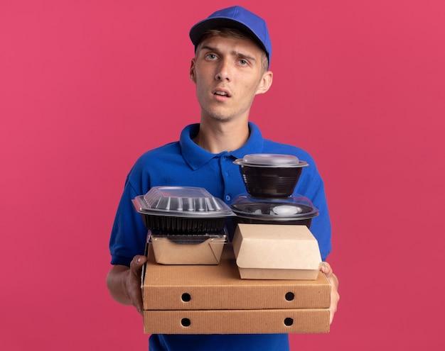 Il ragazzo delle consegne biondo e incapace tiene contenitori per alimenti e pacchi su scatole per pizza isolate su parete rosa con spazio per le copie